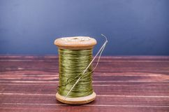 Vintage grunge wooden green thread spool with needle Stock Photo