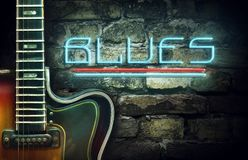 Vintage guitar and a neon inscription Blues on the background of an old brick wall. Concept music. Vintage guitar and a neon inscription JBlues on the stock photo