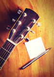 Vintage guitar with paper note. Royalty Free Stock Image