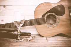 Vintage Guitar with wine bottle and glass on the old wood floor. Royalty Free Stock Photos