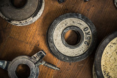 Vintage Gym Weights. Detail Of Some Vintage Gym Dumbbell Weights Against A Rustic Wooden Floor Royalty Free Stock Images