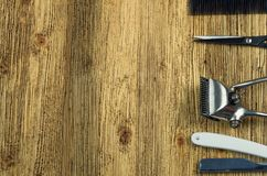 Hairdresser tools on a wooden surface. Vintage hairdressing tools on a rough wooden surface free in the right Royalty Free Stock Images
