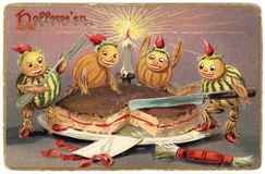 Vintage Halloween Postcard. Antique Halloween postcard from 1910.  Four pumpkin gourd figures cutting a cake illuminated by candlelight Royalty Free Stock Image