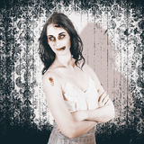 Vintage halloween spook on grunge background. Old Fashion Halloween monster standing with arms folded on grunge wallpaper background in a vintage nightmare Royalty Free Stock Images
