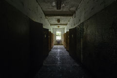 Vintage Hallway and Doors - Abandoned Hospital / Sanitarium - New York. An interior view of a vintage hallway and doors inside an abandoned hospital in New York royalty free stock image