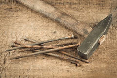 Vintage hammer with nails on wood background Royalty Free Stock Images