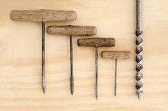 Vintage Hand Drills. Five Vintage Hand drills of various sizes on a wooden background Royalty Free Stock Photos