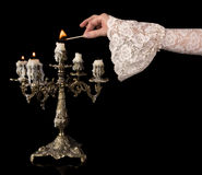 Vintage hand lighting candles. Hand in old-fashioned lace sleeve igniting an antique candlestick Stock Images