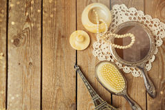 Vintage hand mirror and hairbrush with Eiffel Tower on wooden background. Stock Photos
