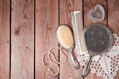 Vintage hand mirror and hairbrush. On wooden background. View from above Stock Photography