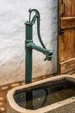 Vintage hand pump with concrete catch dam and wooden door royalty free stock images