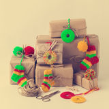 Vintage handmade gifts boxes with small knitted Christmas decora Royalty Free Stock Photos