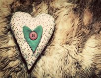 Vintage handmade plush heart pillow on soft blanket Royalty Free Stock Photo