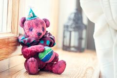 Vintage handmade textile art teddy bear toy-clown. Indoors closeup horizontal image with retro filter Stock Photos