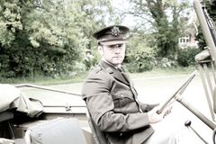 Handsome American WWII GI Army officer in uniform riding Willy Jeep. Vintage Handsome American Soldier, SGT in world war 2 officer`s uniform driving a Willy jeep stock photo