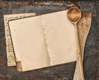 Vintage handwritten recipe book and old kitchen utensils. On rustic metal background. Retro style toned picture Royalty Free Stock Photography