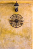 Vintage hanging  clock and lamp on old wall Royalty Free Stock Images
