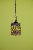 Vintage Hanging Pendant Light on Dark Yellow Green. Single Vintage Hanging Shell Pendant Light with Chain Isolated on Dark Yellow Green Background Stock Photo