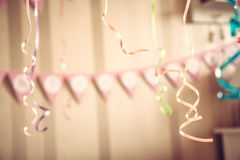 Vintage happy birthday party blurred background with hanging ribbons and garland in decorated room in pastel colors