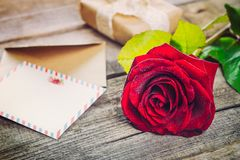 Vintage Happy Valentines Day card. Festive composition with fresh rose flower, post card, envelope and gift box on the rustic wood. En table. Gift for lover Royalty Free Stock Photos