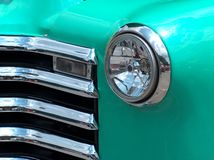 Vintage Headlight. The view of the grill and headlight of a vintage green car Stock Photos