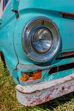 Vintage headlight on an old, abandoned blue van with a rusty bumper royalty free stock photos