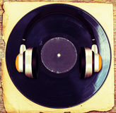 Vintage  headphones   with  gramophone  on old paper and wood. Royalty Free Stock Photos