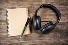 Vintage Headphones and paper note on wood Stock Photos