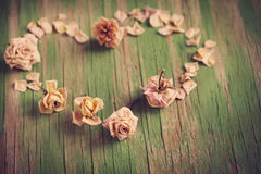 Vintage heart from dry roses on wooden background. Royalty Free Stock Photo