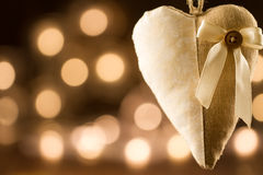 Vintage heart on yellow background defocused lights. Festive decoration. Royalty Free Stock Photo