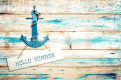 Vintage Hello summer sign hanging with anchor on old wooden blue paint background. Stock Images