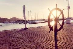 Vintage helm boat steering wheel in esplanade. MAGDALENA, COLOMBIA - FEBRUARY 20, 2015: Vintage decorative helm, boat steering wheel in esplanade during sunset Royalty Free Stock Photos