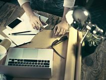 Vintage hipster wooden desktop top view, male hands using a laptop and holding a pencil Stock Photography