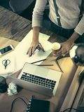 Vintage hipster wooden desktop top view, male hands using a laptop and holding a pencil Stock Images