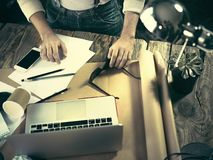 Vintage hipster wooden desktop top view, male hands using a laptop and holding a pencil Stock Photos