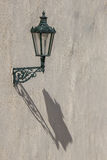 Vintage historical street lamp with long beautiful shadow on whi Royalty Free Stock Photos