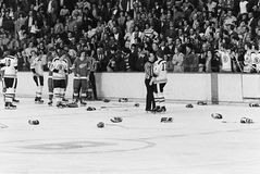 Vintage hockey fight.  Red Wings v. Bruins. The gloves come off as the Boston Bruins and Detroit Red Wings do battle.  (Image from B&W negative Royalty Free Stock Image
