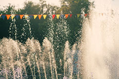 Vintage holidays shot. Jets of a city park fountain and colorful flags. Royalty Free Stock Photo