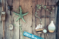 Vintage holidays still life with rope, starfish, compass and bottle on old wooden background Royalty Free Stock Image