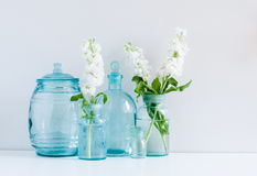 Vintage home decor. Background, white matthiola flowers in different blue glass bottles vases and antique jars on a shelf by the wall Royalty Free Stock Photography