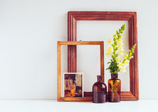 Vintage home decor. Two glass brown bottles with flowers, old wooden frames and a postcard on a white background Stock Image