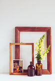 Vintage home decor. Two glass brown bottles with flowers, old wooden frames and a postcard on a white background Stock Images