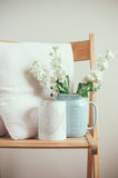 Vintage home decor. White matthiola flowers in a blue jug on a chair with pillows by the wall Royalty Free Stock Images