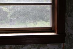 Vintage home window looking out on an abandoned homestead. Dirty and abandoned looking home with view out grimy window to rustic homestead stock photo