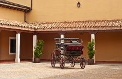 Court yard and carriage of a southeastern winery in Spain. Vintage horse drawn carriage in the courtyard of a southeastern winery in Spain, on a cloudy, summer royalty free stock image