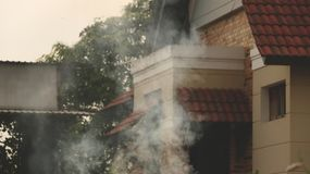 Vintage House Door and Windows Details with Tile Roofs. Smoke in Foreground Stock Images