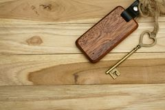 Vintage house key with wooden home keyring on wood board background, property concept, copy space. Vintage house key with classic wooden home keyring on wood stock image