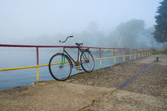 Vintage house in Lviv city. Old bicycle on the pier near the lake in the fog royalty free stock images