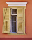 Vintage house pale yellow shutters window. On colorful wall Royalty Free Stock Photography