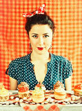 Vintage housewife and cupcakes. Vintage image with the housewife and cupcakes on the orange background Royalty Free Stock Image